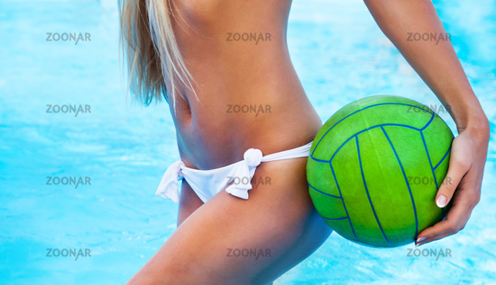 Sexy girl near the pool holding green ball
