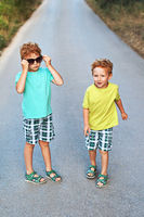 Two cute red curly boys brothers are having fun with mother sunglasses
