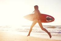 Hot surfer girl at sunset