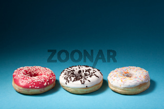 three donuts with color icing isolated on blue background with copyspace