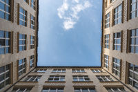 A look up at a white cloud from a courtyard