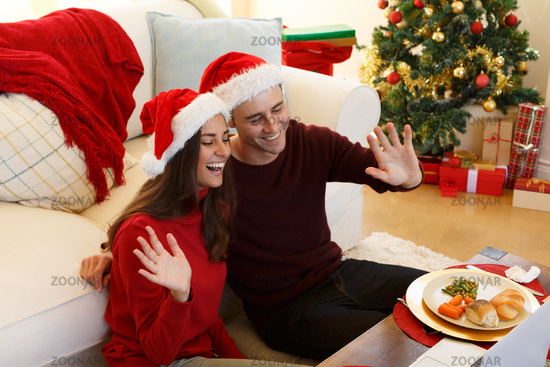 Couple wearing santa hat smiling and waving while having a video call on laptop in the living room