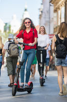 Trendy fashinable teenager girls riding public rental electric scooters in urban city environment. New eco-friendly modern public city transport in Ljubljana, Slovenia