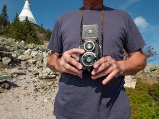 Close up of old man hand holding vintage film camera