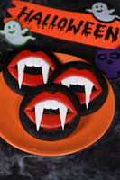 Vampire fangs protruding from scarlet lips, Glazed honey gingerbread cookies. Halloween food idea