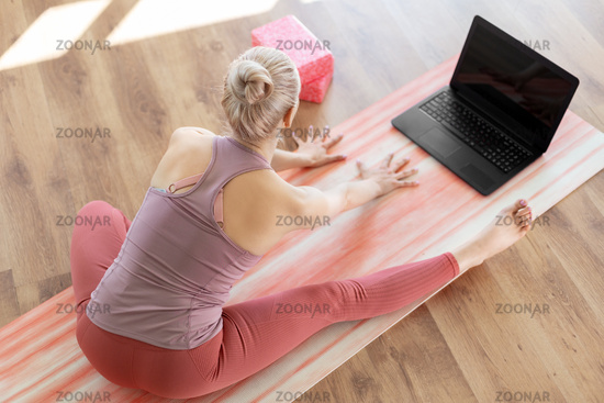 woman with laptop exercising at yoga studio