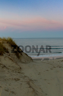 wild coast and ocean with large sand dunes at sunrise