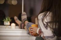 Anonymous woman relaxing with hot drink in evening