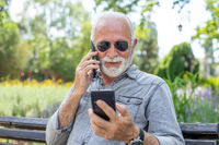Old man compare two smartphones
