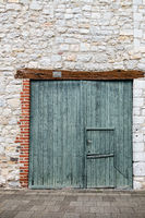 Old green double-hung barn door with wooden lintel.