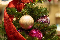 Christmas background with fir tree branches, decorations and blurred lights on back. Close-up view of beautiful christmas tree with colorful balls and illuminated garland