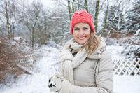 Glückliche Frau im Winter steht im Garten