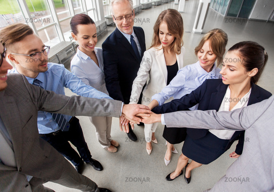 happy business people stacking hands at office