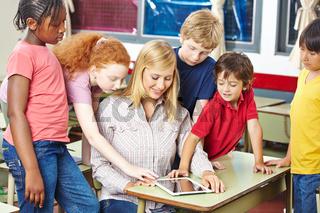 Lehrer und Schüler schauen auf Tablet Computer