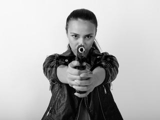 Close up of young Asian woman aiming handgun at camera with both hands against white background