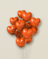 Orange heart shape air balloons group on a beige background