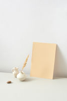 Ceramic vases with dry natural twig and vertical paper sheet on a light grey background.
