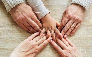 Hand von Kleinkind und Hände von Erwachsenen