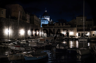 Dubrovinik harbour with boats along the wall at night, Croatia