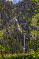 Small waterfall in the mountains, green meadow in the foreground