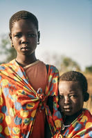 BOYA TRIBE, SOUTH SUDAN - MARCH 10, 2020: Children from Boya Tribe wearing pieces of bright fabric and looking at camera while standing on blurred background of savanna on sunny day in South Sudan, Africa