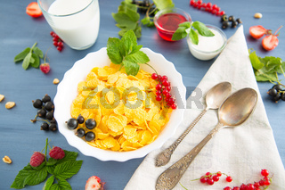 bowl of granola with yogurt and berries isolated on white background, top view Healthy tasty breakfast cornflakes with strawberries, raspberries, black currants and red currants.
