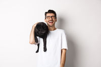 Happy young man laughing carefree, holding cute black dog, pug breed, on shoulder and having fun, standing over white background