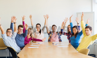 group of smiling students raising hands in office
