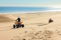 Quad driving people - two happy bikers in sand desert dunes at ocean coast beach, Africa, Namibia, Namib, Walvis Bay, Swakopmund.