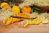 A cutting board with a vanilla pod, a sliced organic lemon and organic orange and elderflower