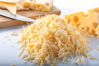 Pieces of Swiss cheese and grated cheese with a knife and a wooden board