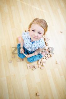 Kind spielt mit Bausteinen auf dem Boden