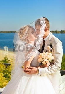 Loving bride and groom sheltered veil bride