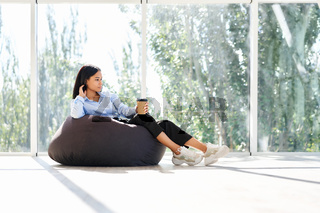 Pretty african american woman relaxing on bean bag chair with cup of coffee
