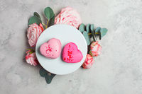 The pair delicate heart shaped macaroons with bouquet