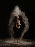 Young woman dancing in dust profile shot
