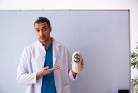 Young male doctor in presentation concept