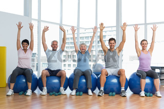Class sitting on exercise balls and raising hands in gym