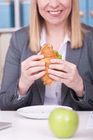 Woman at the office eating food in her break. Business, diet and healthy lifestyle concept.