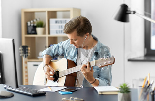 man with earphones and smartphone playing guitar