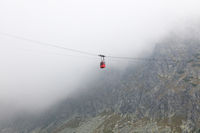Red mountain cableway car in clouds and fog