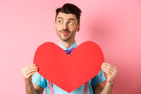 Valentines day concept. Dreamy romantic man looking left and showing big red heart cutout, standing on pink background