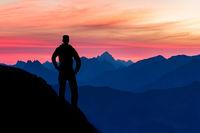 Silhouette of hiking man enjoying beautiful blue mountain ranges silhouettes and pink clouds. Alps, Allgau, Tirol, Austria.