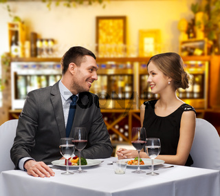 smiling couple with food and wine at restaurant