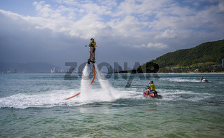 Flying on a flyboard on Winpearl beach with a view of the city of Nha Trang in Vietnam. January 18, 2020