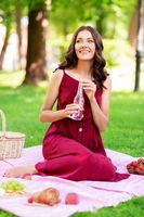 happy woman with picnic basket and drink at park