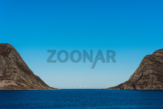 U-shaped mountains siding a fjord on the coast of Norway on clear sunny day with blue sky