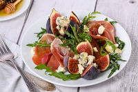 Appetizer arugula with Parma ham and fresh figs stuffed blue cheese, honey