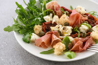 Salad arugula, Parma ham with sun-dried tomatoes, mozzarella slices, croutons, capers, seasoned oil