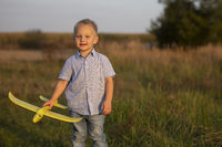 Little boy in the field plays with an airplane.